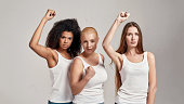 Portrait of three young diverse women wearing white shirts having confident look while showing, raising clenched fist, posing together isolated over grey background. Protection of rights concept
