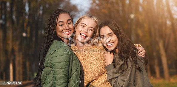 Portrait of three international young girlfriends spending time in park, panorama