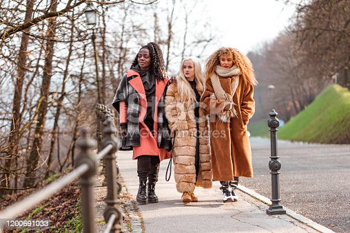 Portrait of three young women, two caucasian and one african american, outdoors in wintertime.