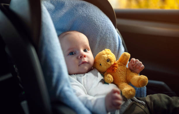 Portrait of toddler boy sitting in car seat. Child transportation safety stock photo