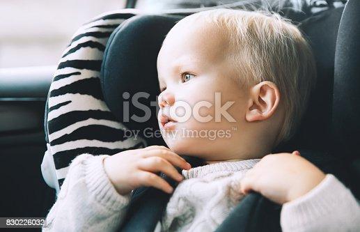 istock Portrait of toddler boy sitting in car seat. 830226032