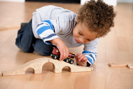 A portrait of a toddler playing with a train track in the living room.