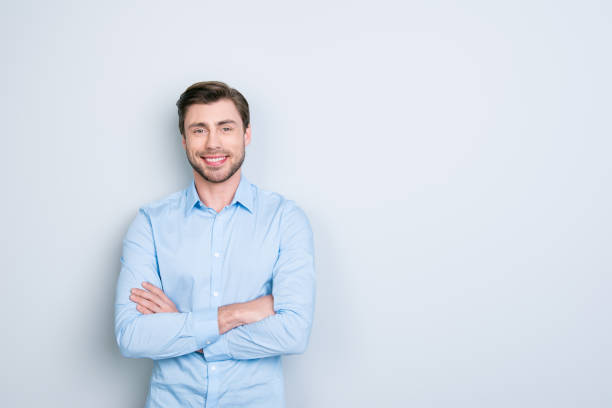 牙齒英俊的鬍子經理的肖像與交叉的手在灰色背景。快樂的傢伙正在看鏡頭。 - 衣領 個照片及圖片檔