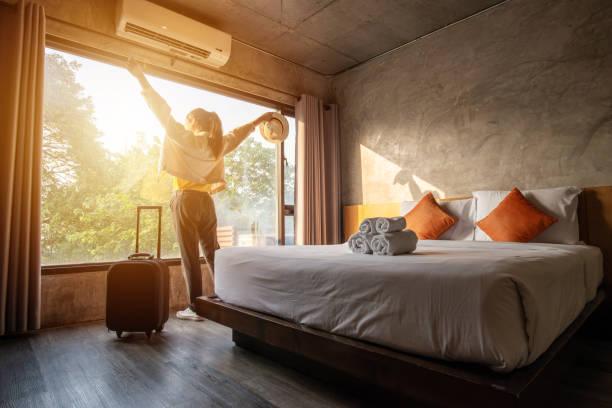 portret turystki podniósł ręce i stał prawie okno, patrząc na piękny widok z bagażem w pokoju hotelowym po zameldowaniu. - hotel zdjęcia i obrazy z banku zdjęć