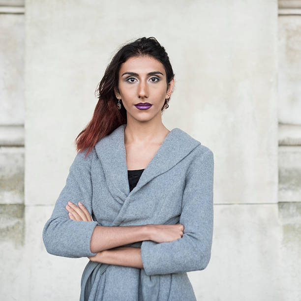 Portrait of transgender female facing camera, arms folded Attractive transgender female looking towards camera, confident female wearing grey top. Turkish, Middle Eastern ethnicity transgender stock pictures, royalty-free photos & images