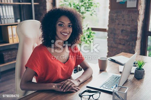 Portrait of trendy charming attorney with beaming smile in casual outfit sitting at desk in modern office looking at camera. People person profession vector concept