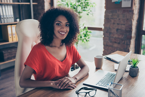 istock Portrait of trendy charming attorney with beaming smile in casual outfit sitting at desk in modern office looking at camera. People person profession vector concept 979009470