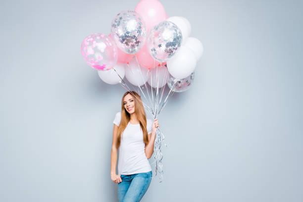 porträt von trendigen nettes mädchen mit langen haaren im casual-outfit mit rosa und weißen luftballons in der hand blick in die kamera, die auf grauem hintergrund isoliert - ballonhose stock-fotos und bilder