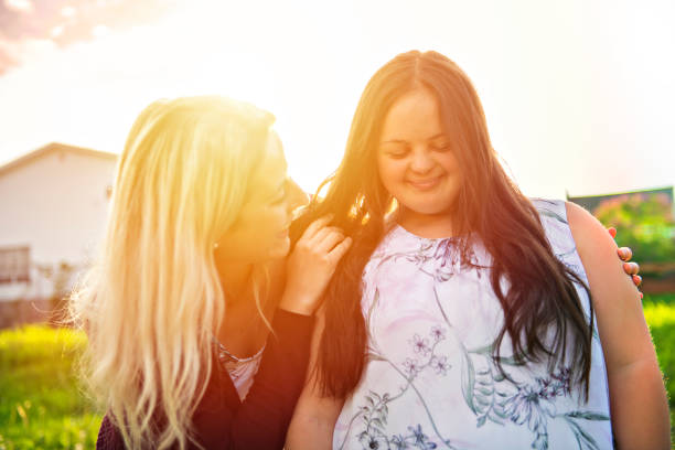 A Portrait of trisomie 21 adult girl smilin outside at sunset with family friend stock photo