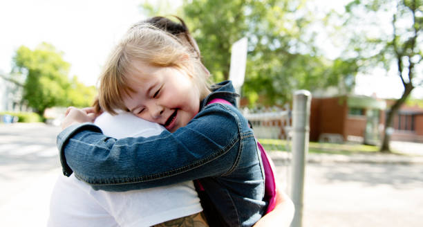 a portrait of trisomie 21 child girl outside hugging his mother on a school playground - handicapped imagens e fotografias de stock