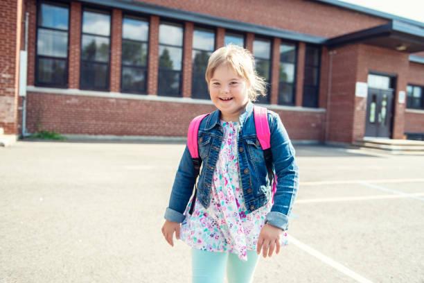 Ein Porträt von Trisomie 21 Kind Mädchen draußen auf einem Schulspielplatz – Foto