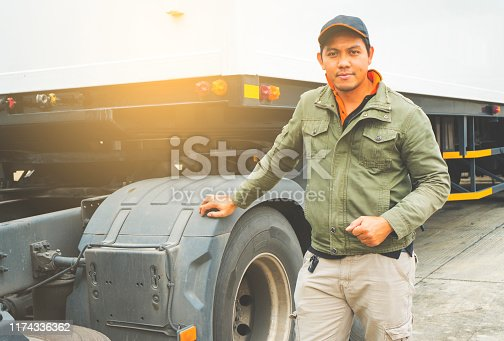 Portrait of truck driver with semi truck trailer, freight industry logistics and transport