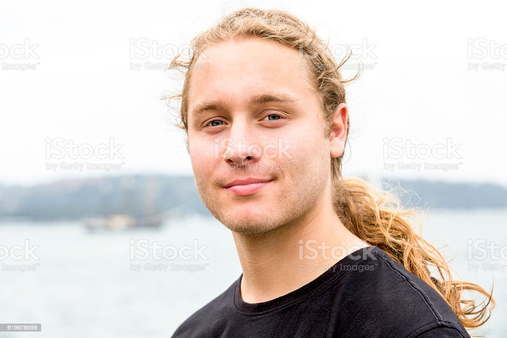 Portrait of twenty years old young man with ponytail, outdoor - foto de acervo