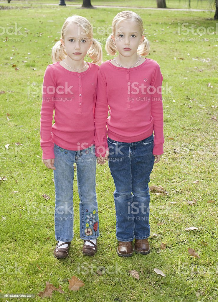 Portrait of twin sisters (6-7) in park foto de stock royalty-free