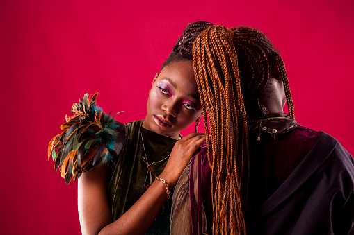 Portrait of Two African American Black Women with braided hair, fashion studio shot, red background