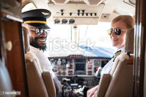 Portrait of two airplane pilots looking over shoulder in a private jet