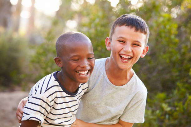 portrait of two boys embracing and laughing hard outdoors - bambini maschi foto e immagini stock