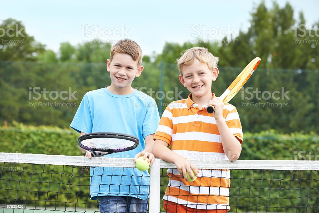 Portrait Of Two Boys Playing Tennis Together stock photo