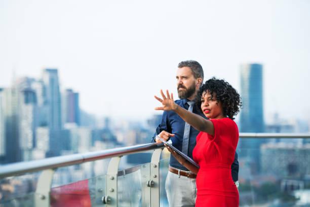 ein porträt von zwei geschäftsleuten gegen london ansicht panorama stehen, sprechen. - rotes oberteil stock-fotos und bilder