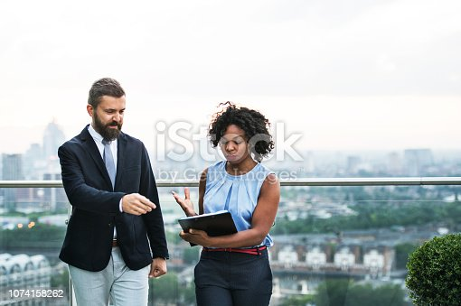 istock A portrait of two businesspeople standing against London view panorama. 1074158262