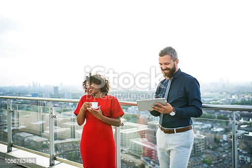 istock A portrait of two businesspeople with tablet standing against London view panorama. 1056763484