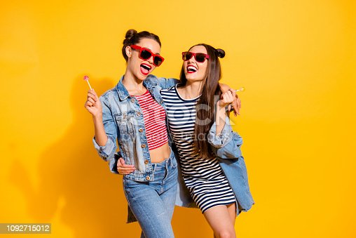 1092709104 istock photo Portrait of two careless carefree stylish trendy brunette hair lady isolated on yellow vivid background in glasses spectacles hold sugar sweet yummy calories caramel confectionery dessert in hands 1092715012