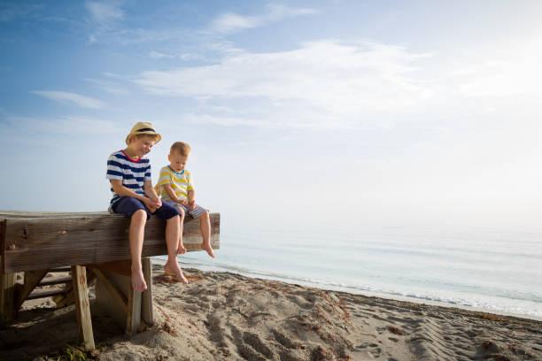 porträtt av två barn koppla av vid havet sitter på kanten av en trä brygga med havs botten. solig och glädjefylld sommar dag. - flod vatten brygga bildbanksfoton och bilder