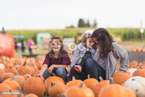 Two young girls sit on pumpkins at a farm and smile at the camera. Their mom is crouching by the older one and smiling at her.