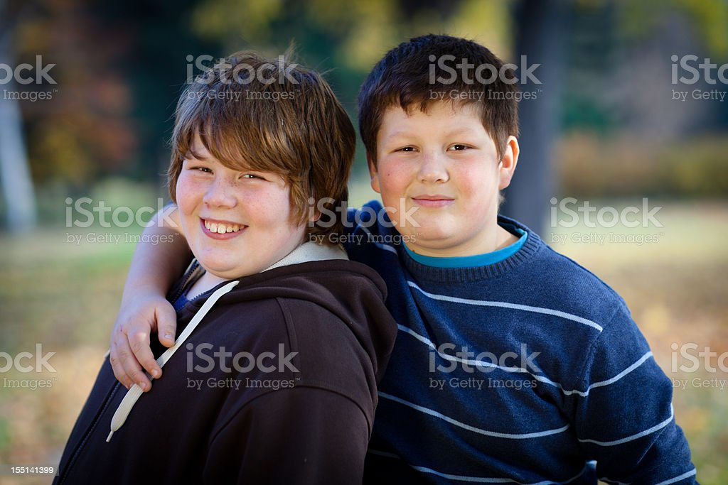 portrait of two cute overweight boys, arms around stock photo