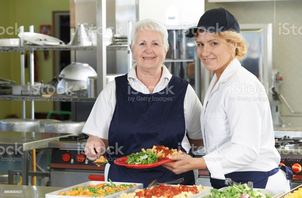 Portrait Of Two Dinner Ladies In School Cafeteria stock photo