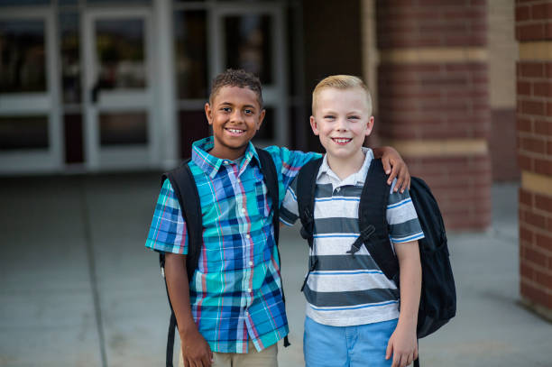 Portrait of Two diverse school kids standing outside their elementary school building stock photo