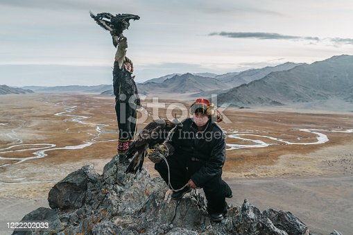 Portrait of two eagle hunters in Mongolia  on the background of river