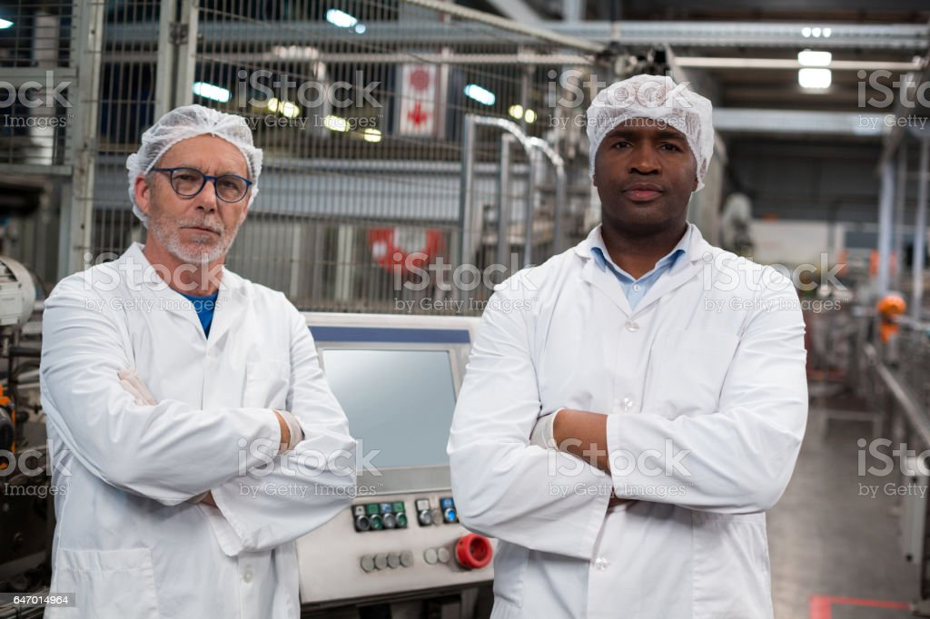 Portrait of two factory engineers standing with arms crossed stock photo