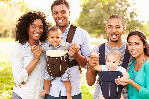 Portrait Of Two Families With Baby Carriers In Park stock photo