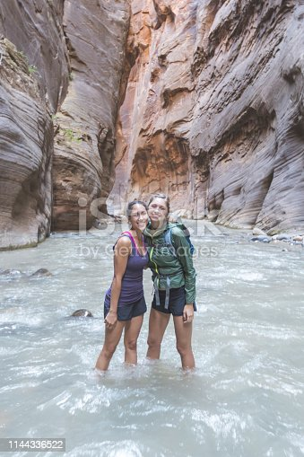 Two millennial-age females stand in knee-deep water in a canyon and smile toward the camera. Red canyon walls are rising up on either side.