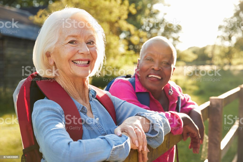 Portrait Of Two Female Senior Friends Hiking In Countryside stock photo