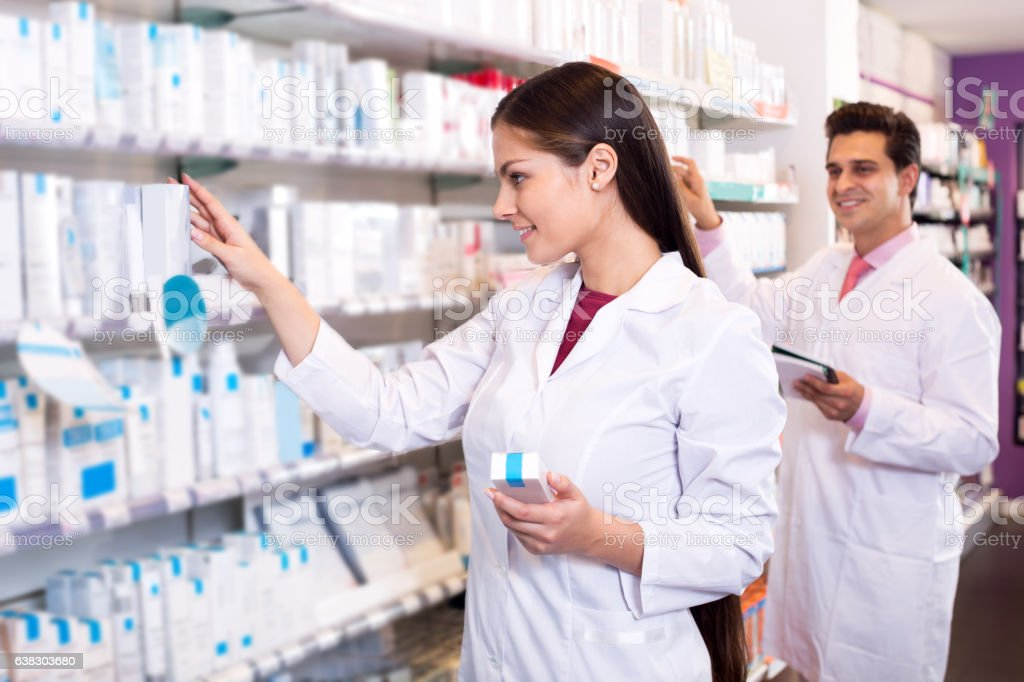 Portrait of two friendly pharmacists working stock photo