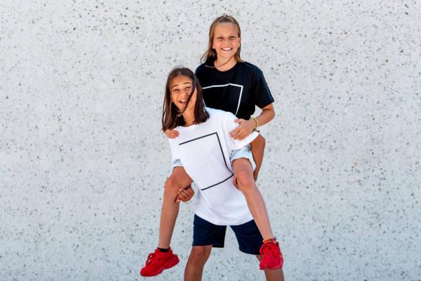 Porträt von zwei Mädchen Huckepack Reiten – Foto