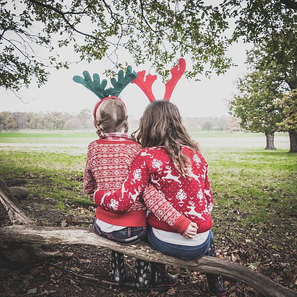portrait of two girls wearing antlers, arms around each other - weihnachten 7 jährige stock-fotos und bilder