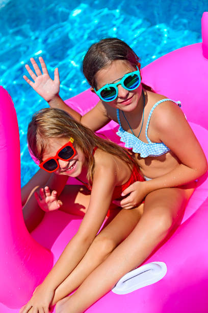 portrait of two girls wearing sunglasses, happy friends on inflatable flamingo swim float - children play water park stock photos and pictures
