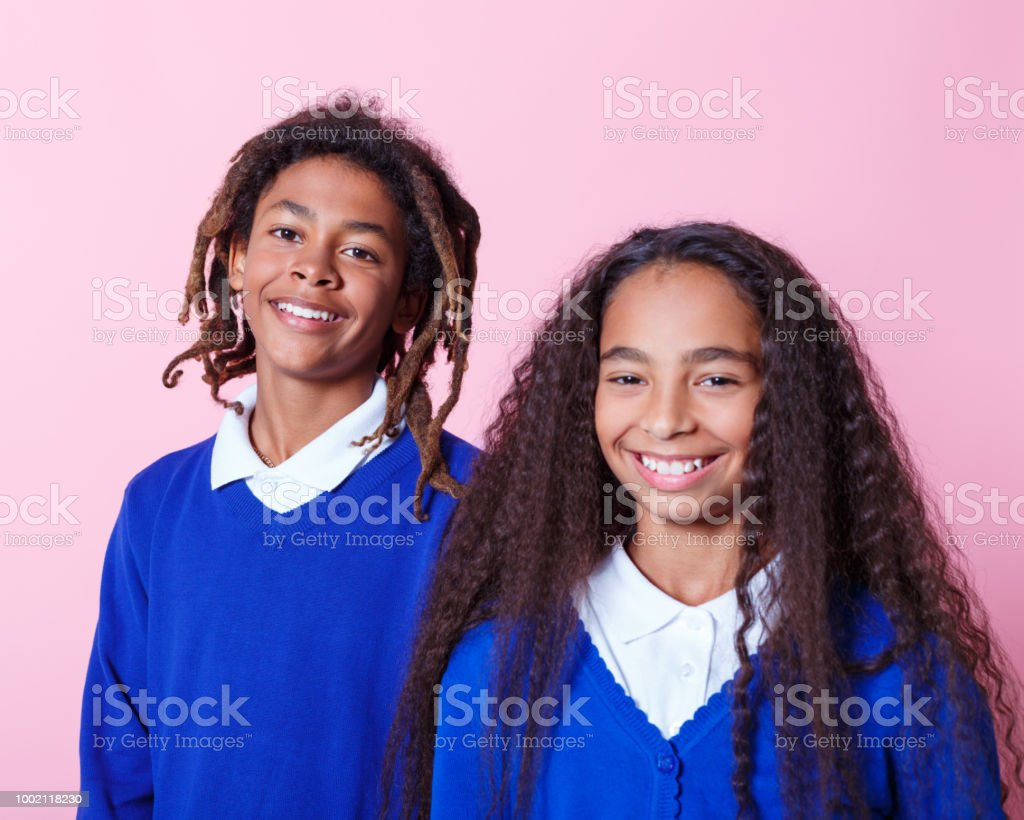 Portrait of two happy afro amercian teenage students Two afro American teenagers wearing school uniforms smiling at camera. Studio shot, pink background. 10-11 Years Stock Photo