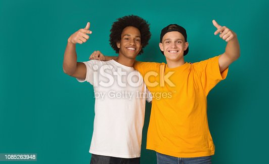 istock Portrait of two happy friends pointing fingers at camera 1085263948