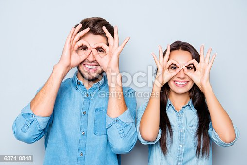 1092709104istockphoto Portrait of two happy funny lovers holding fingers near eyes 637410848