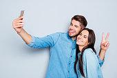 Portrait of two happy lovers making selfie on smartphone
