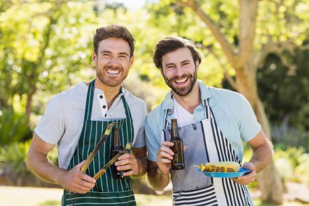 porträt von zwei glückliche männer halten grill essen und bier flasche - grillschürze stock-fotos und bilder