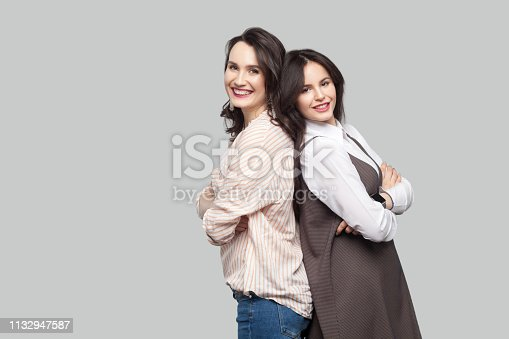 Portrait of two happy satisfied beautiful partners in casual style standing back to back with crossed arms and looking at camera with toothy smile. indoor studio shot, isolated on grey background.