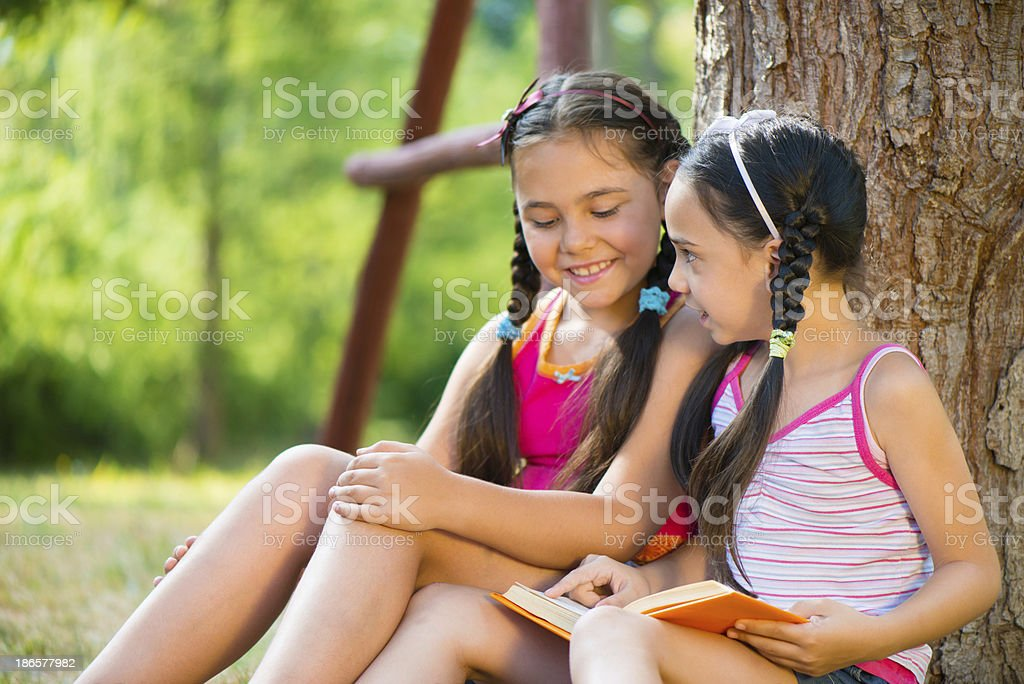 Portrait of two happy sisters reading in the park royalty-free stock photo