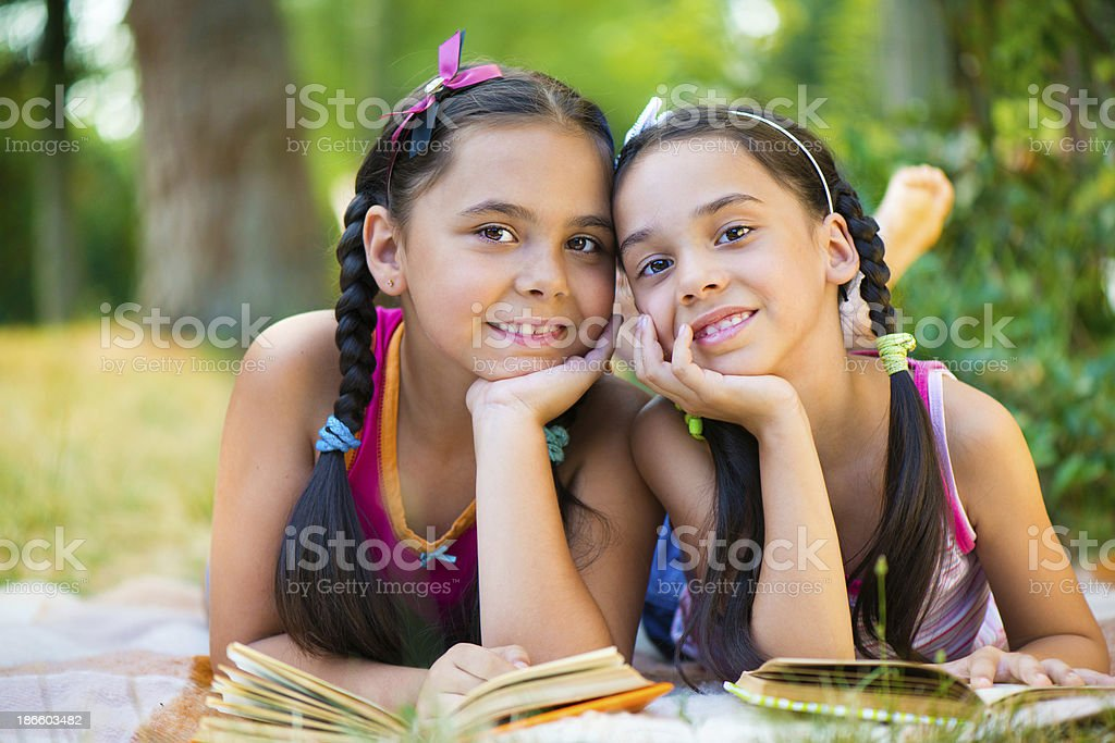 Portrait of two hispanic sisters reading in the park royalty-free stock photo