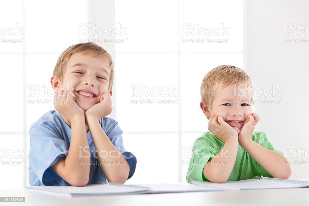 Portrait of two little boys sitting by the table stock photo