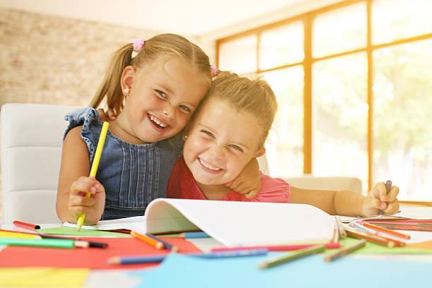 portrait of two little girl drawing and looking at camera. - zeichnen lernen mit bleistift stock-fotos und bilder